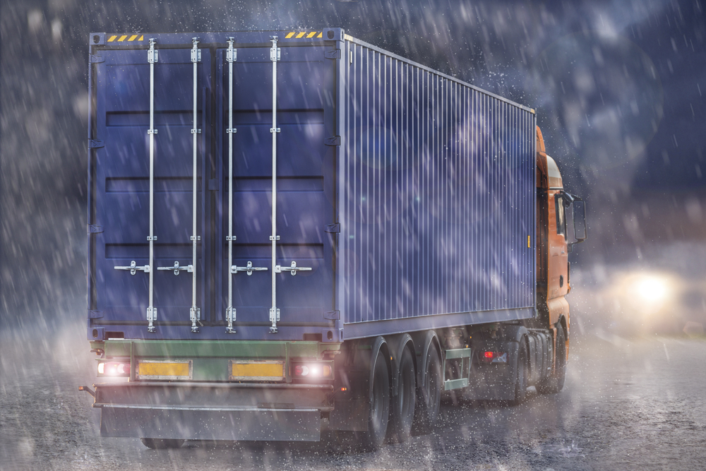 truck carrying blue storage container in rain