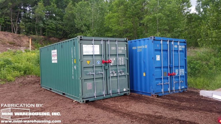 side view of two blue storage containers at construction site